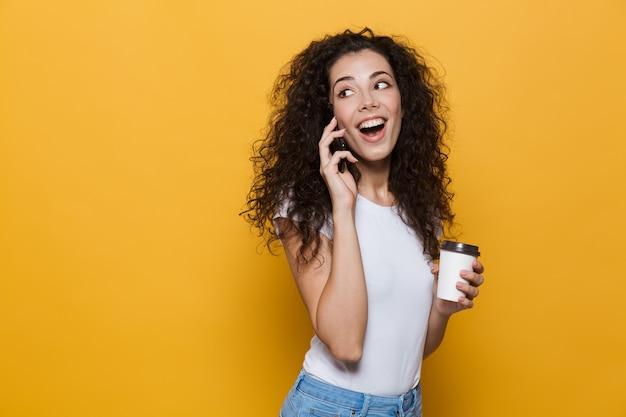 Młoda europejska kobieta w wieku 20 lat z kręconymi włosami rozmawia przez telefon komórkowy i trzyma kawę na wynos w papierowym kubku na żółto