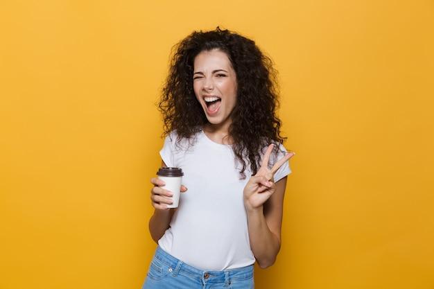Młoda europejska kobieta w wieku 20 lat z kręconymi włosami uśmiecha się i trzyma kawę na wynos w papierowym kubku na żółto
