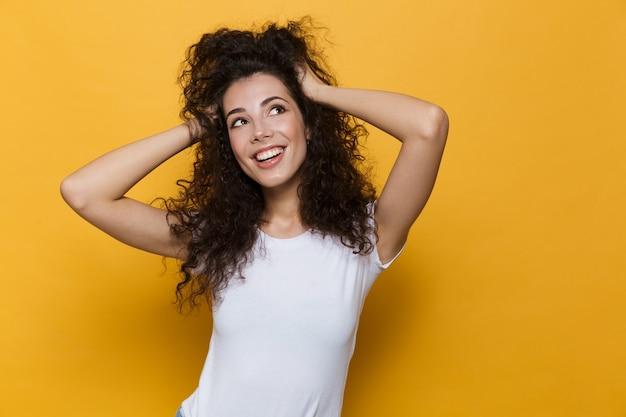 Młoda europejska kobieta w wieku 20 lat z kręconymi włosami uśmiechnięta i chwytająca głowę odizolowana na żółto