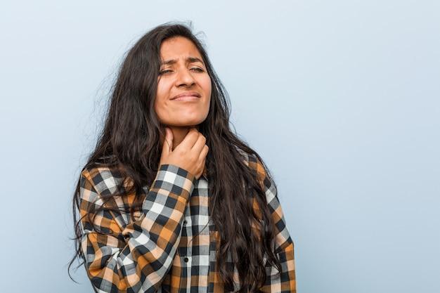 Młoda fajna indyjska kobieta cierpi na ból gardła z powodu wirusa lub infekcji.