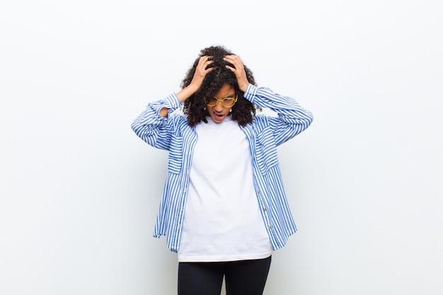 Młoda fajna kobieta czuje się zestresowana i sfrustrowana, podnosząc ręce do głowy, czując się zmęczona, nieszczęśliwa i z migreną