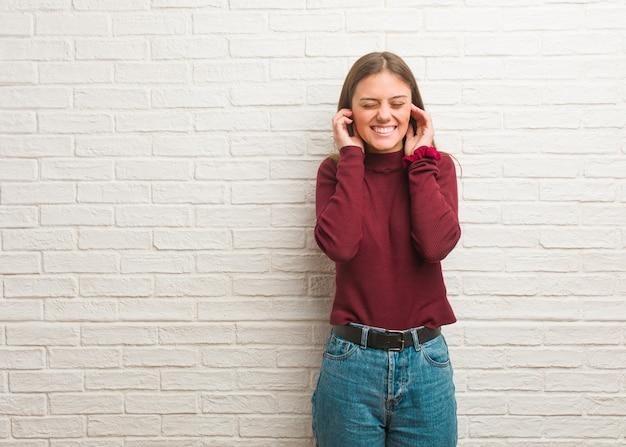 Młoda fajna kobieta na ścianie cegły obejmujące uszy rękami