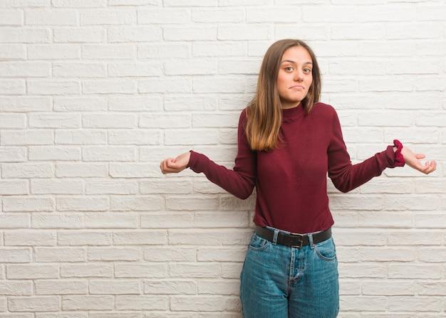 Młoda fajna kobieta ponad ścianą z cegieł wątpi i wzrusza ramionami