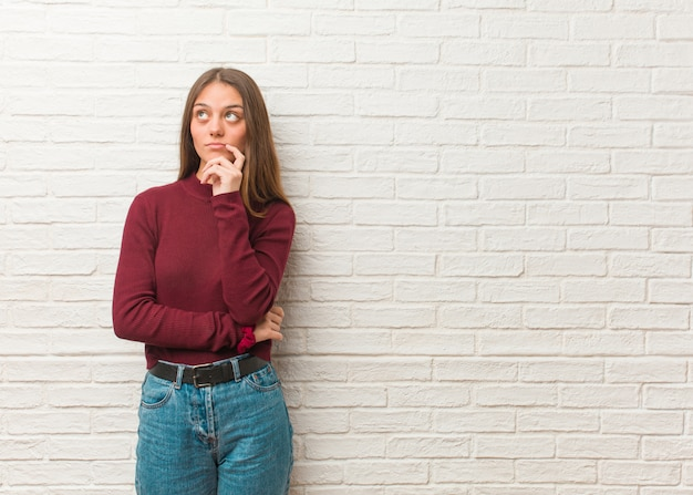 Młoda fajna kobieta ponad ścianą z cegieł wątpi i zagubiona