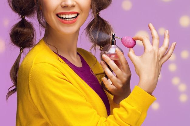 Młoda fantazyjna kobieta stosując perfumy
