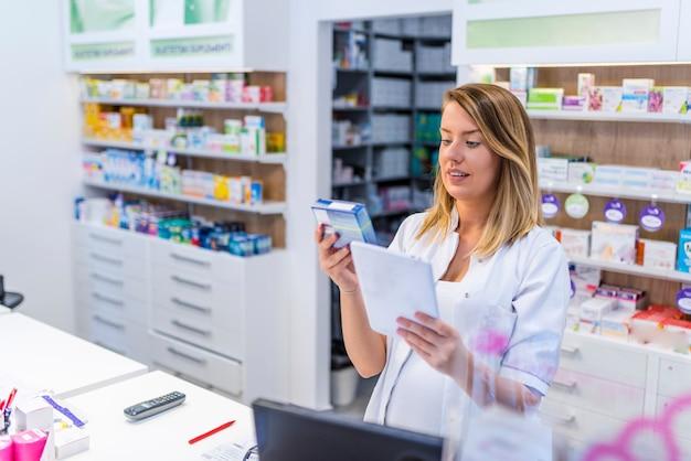 Młoda farmaceuta trzyma pastylkę i pudełko lekarstwa.