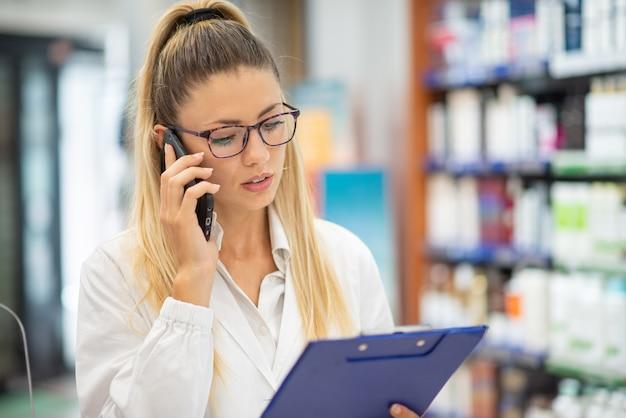 Młoda farmaceutka rozmawia przez telefon podczas czytania recepty