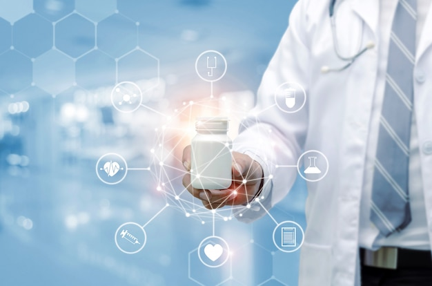 Młoda farmaceuty lekarka trzyma białą medycyny butelkę z stetoskop ręką
