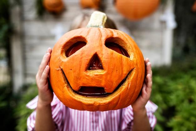 Młoda figlarna dziewczyna bawiąca się w halloween