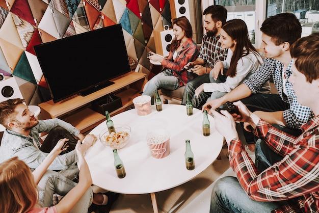 Młoda firma grająca w gry wideo na imprezie