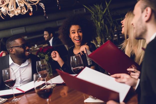 Młoda firma siedzi razem w restauracji.