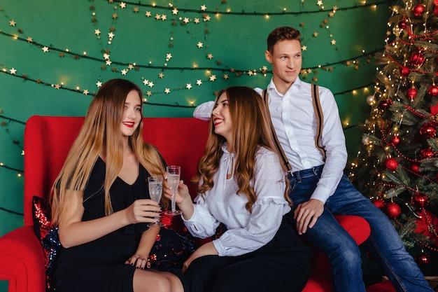 Młoda firma z dwiema dziewczynami i jednym facetem świętuje nowy rok z kieliszkami szampana