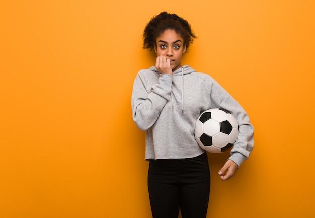 Młoda fitness czarna kobieta obgryzająca paznokcie, nerwowa i bardzo niespokojna