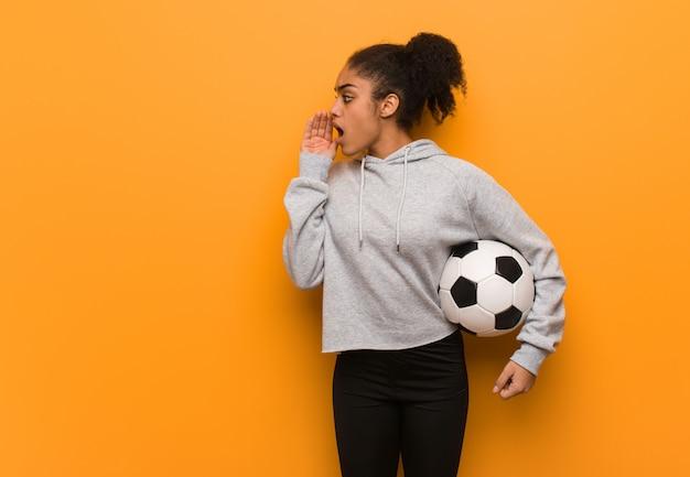Młoda fitness czarna kobieta szepcząc plotek podtekst. trzymać piłkę nożną.