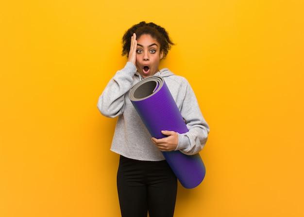 Młoda fitness czarna kobieta zaskoczona i zszokowana. trzymać matę.