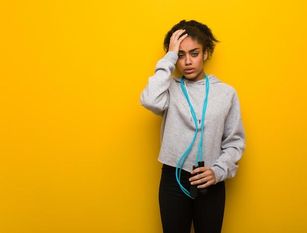 Młoda fitness czarna kobieta zmęczona i bardzo senna. trzymanie skakanki.