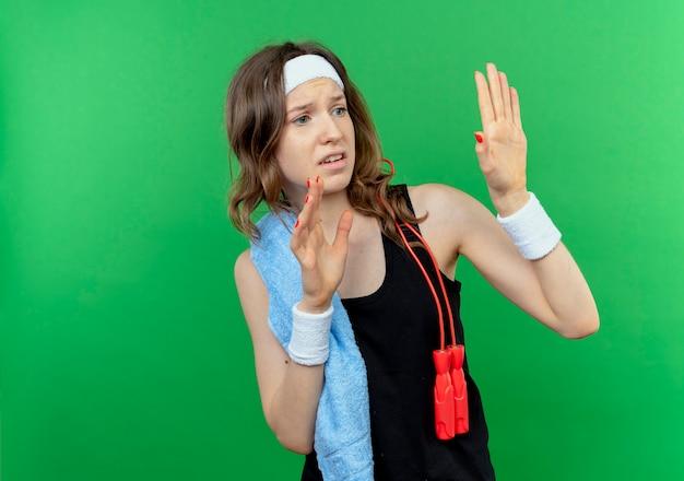 Młoda fitness dziewczyna w czarnej odzieży sportowej z opaską i ręcznikiem na ramieniu, wyciągając ręce, mówiąc, że nie podchodzi bliżej, boi się zieleni