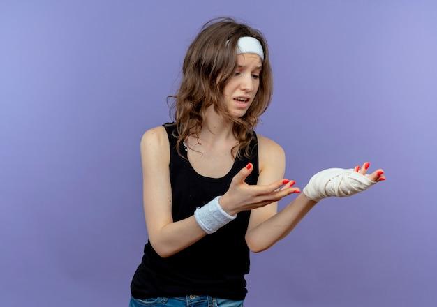 Młoda fitness dziewczyna w czarnej odzieży sportowej z opaską patrzy na jej zabandażowany nadgarstek, zdezorientowany i niezadowolony, stojąc nad niebieską ścianą
