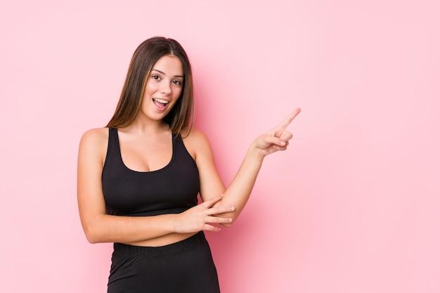 Młoda fitness kaukaski kobieta na białym tle uśmiechnięty wesoło wskazując palcem wskazującym daleko.