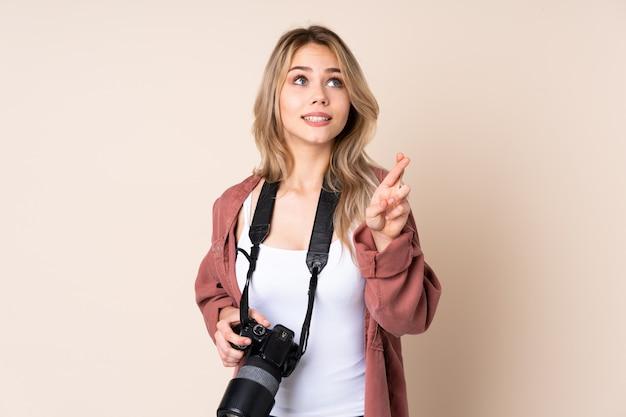 Młoda fotograf dziewczyna nad ścianą z palcami krzyżującymi i życzącymi najlepszego