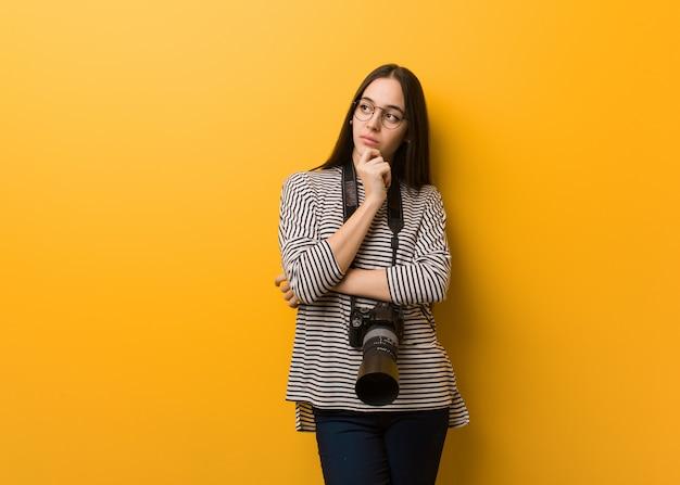 Młoda fotograf kobieta myśleć o pomysle