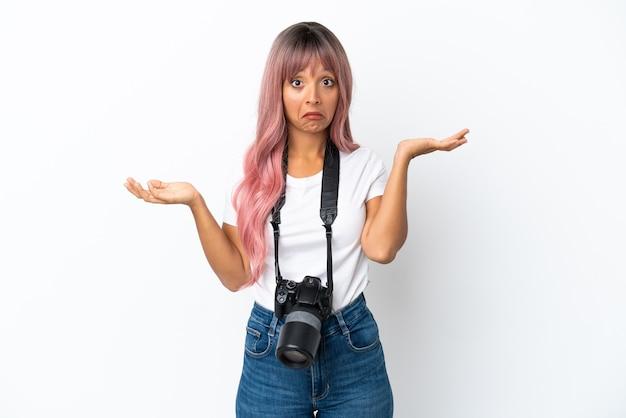 Młoda fotografka mieszanej rasy kobieta z różowymi włosami na białym tle mająca wątpliwości podczas podnoszenia rąk