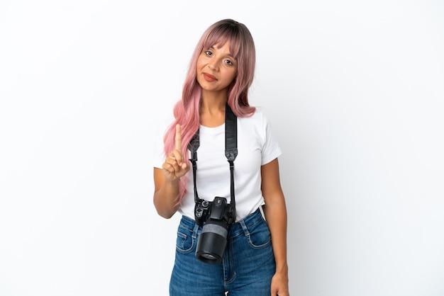 Młoda fotografka mieszanej rasy kobieta z różowymi włosami na białym tle pokazująca i unosząca palec