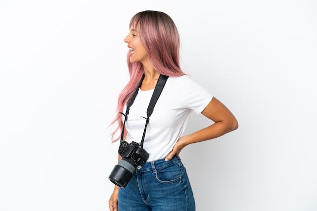Młoda fotografka mieszanej rasy kobieta z różowymi włosami na białym tle śmiejąca się w pozycji bocznej