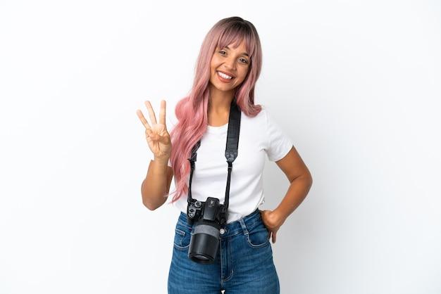 Młoda fotografka mieszanej rasy kobieta z różowymi włosami na białym tle szczęśliwa i licząca trzy palcami