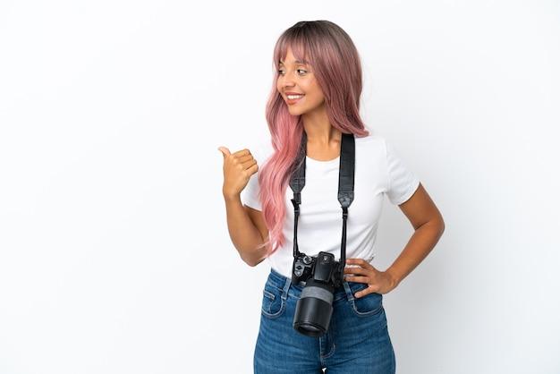 Młoda fotografka mieszanej rasy kobieta z różowymi włosami na białym tle wskazująca na bok, aby zaprezentować produkt