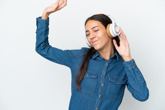 Młoda francuska dziewczyna na białym tle słuchając muzyki i tańcząc
