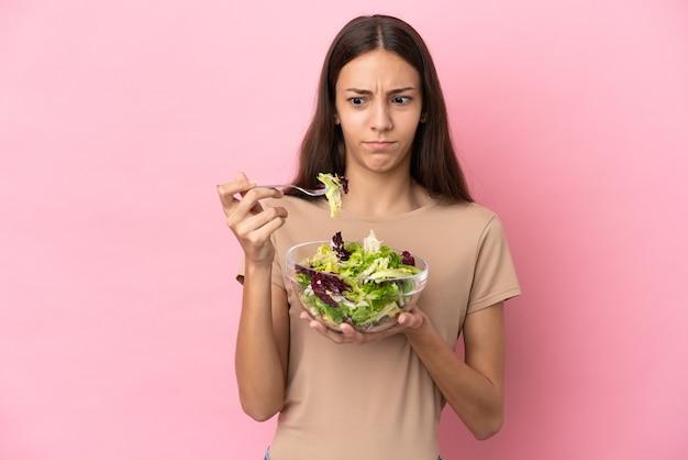 Młoda francuska dziewczyna na białym tle trzyma miskę sałatki ze smutnym wyrazem twarzy
