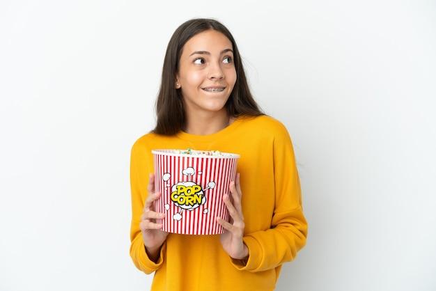 Młoda francuska dziewczyna na białym tle trzymająca duże wiadro popcornów