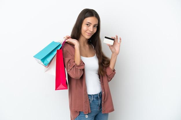 Młoda francuska dziewczyna na białym tle trzymająca torby na zakupy i kartę kredytową