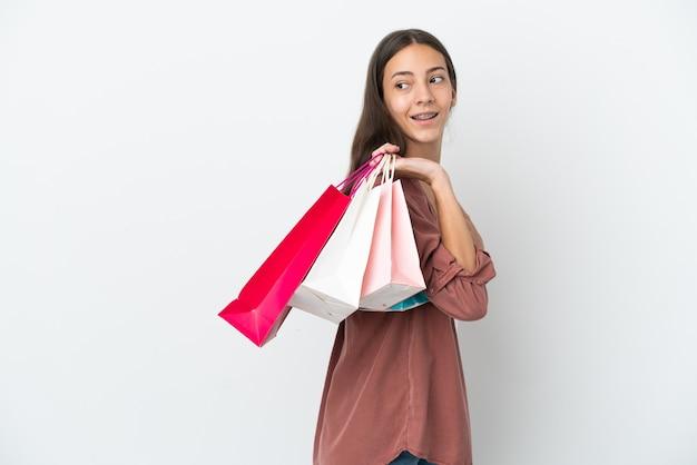 Młoda francuska dziewczyna na białym tle trzymająca torby na zakupy i uśmiechnięta