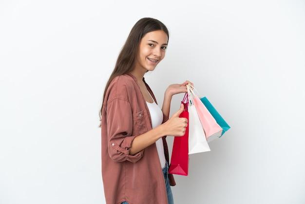 Młoda francuska dziewczyna na białym tle trzymająca torby na zakupy i z kciukiem do góry