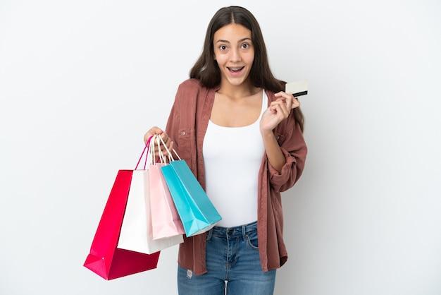 Młoda francuska dziewczyna na białym tle trzymająca torby na zakupy i zaskoczona