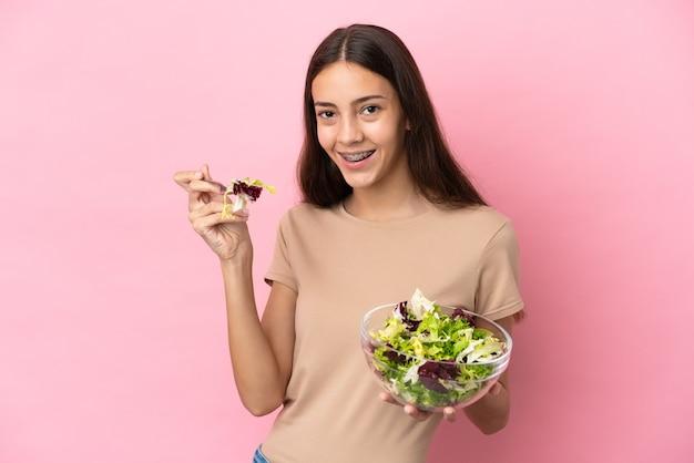 Młoda francuska dziewczyna na różowym tle trzymająca miskę sałatki ze szczęśliwym wyrazem twarzy