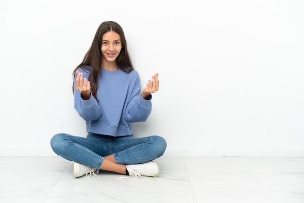 Młoda francuska dziewczyna siedzi na podłodze robiąc gest pieniędzy