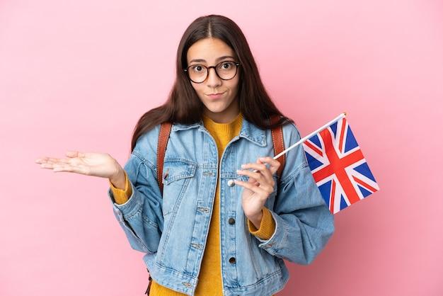 Młoda francuska dziewczyna trzyma flagę wielkiej brytanii na białym tle na różowym tle, mając wątpliwości podczas podnoszenia rąk