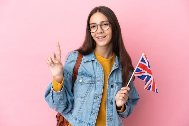 Młoda francuska dziewczyna trzyma flagę zjednoczonego królestwa na białym tle na różowym tle pokazując i podnosząc palec na znak najlepszych