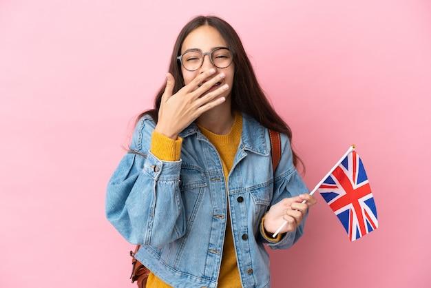 Młoda francuska dziewczyna trzyma flagę zjednoczonego królestwa na białym tle na różowym tle szczęśliwa i uśmiechnięta obejmująca usta ręką
