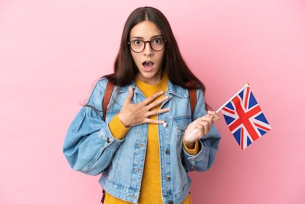 Młoda francuska dziewczyna trzymająca flagę wielkiej brytanii na białym tle na różowym tle zaskoczona i zszokowana, patrząc w prawo