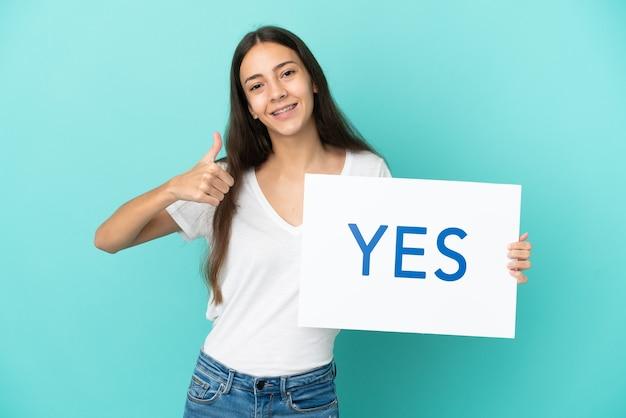 Młoda francuzka na białym tle na niebieskim tle trzyma tabliczkę z tekstem tak z kciukiem do góry