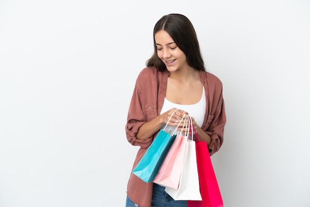 Młoda francuzka na białym tle trzymająca torby na zakupy i zaglądająca do środka