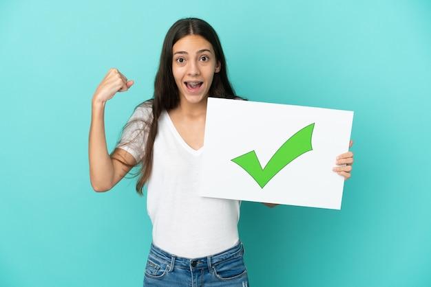 Młoda francuzka odizolowana na niebieskim tle trzyma afisz z tekstem zielona ikona znacznika wyboru i świętuje zwycięstwo