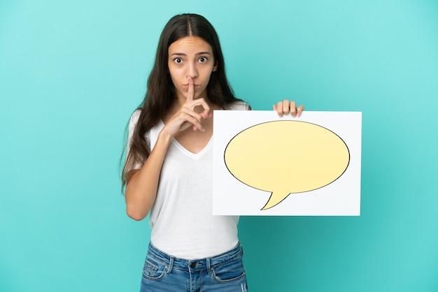 Młoda francuzka odizolowana na niebieskim tle trzymająca afisz z ikoną dymka robi gest ciszy