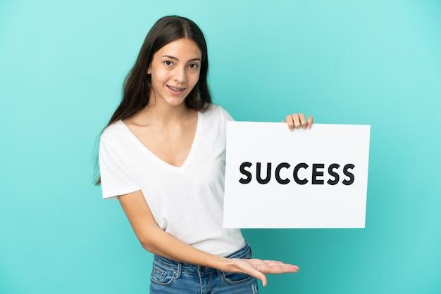 Młoda francuzka odizolowana na niebieskim tle trzymająca afisz z tekstem sukces ze szczęśliwym wyrazem