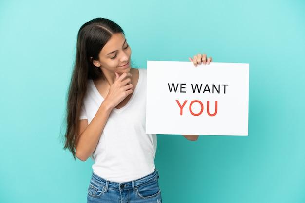 Młoda francuzka odizolowana na niebieskim tle trzymająca deskę we want you ze szczęśliwym wyrazem twarzy