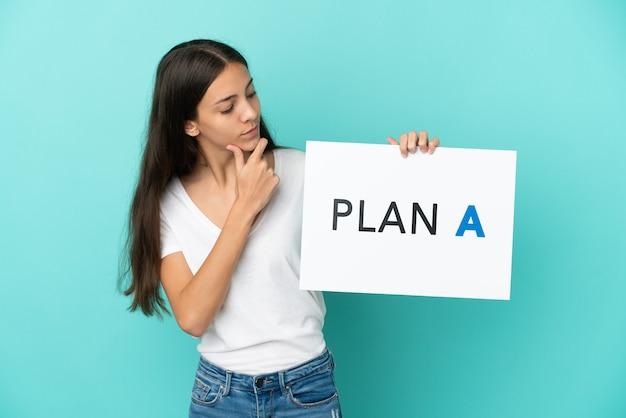 Młoda francuzka odizolowana na niebieskim tle trzymająca tabliczkę z napisem plan a i myśląca